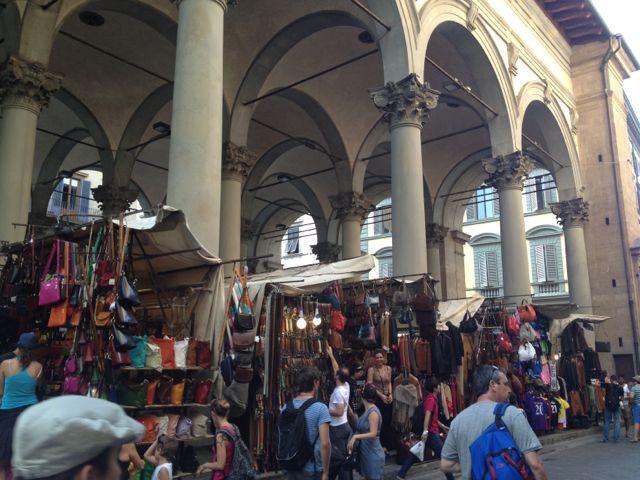 Camelôs vendendo couro e casaco de pele do lado de fora do mercado